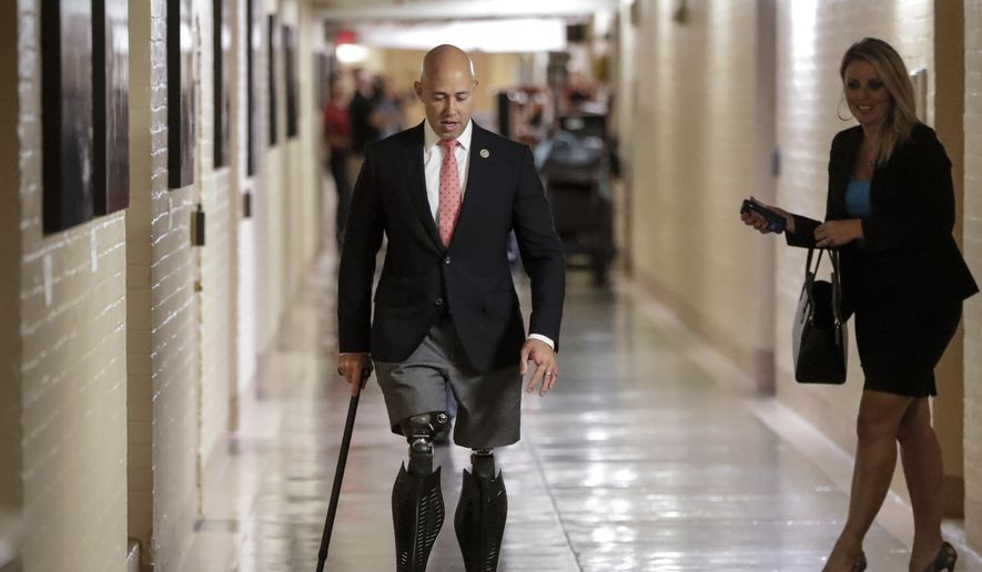 Rep. Brian Mast, R-Fla., walks to a meeting with fellow Republicans on Capitol Hill in Washington, Friday, July 14, 2017, to reconcile the GOP's long-overdue budget blueprint, even as divisions between moderates and conservatives over cutting programs like food stamps threaten passage of the measure. Mast, a combat veteran and bomb disposal technician, lost both legs in an IED explosion as he was clearing a path for Army Rangers in Afghanistan in 2010. (AP Photo/J. Scott Applewhite) **FILE**