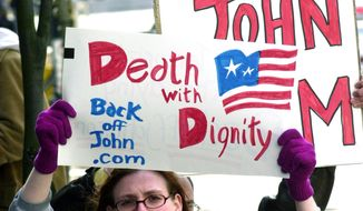 Stacey Richter holds a sign outside a federal courthouse in Portland, Ore., as a hearing begins to decide the fate of Oregon's physician-assisted suicide law. Voters approved the aid-in-dying proposal in 1994 and it then survived a repeal effort. The law that took effect Oct. 27, 1997 made Oregon the first state to make it legal for a doctor to prescribe a life-ending drug to a terminally ill patient of sound mind who makes the request. (AP Photo/Don Ryan, File) **FILE**