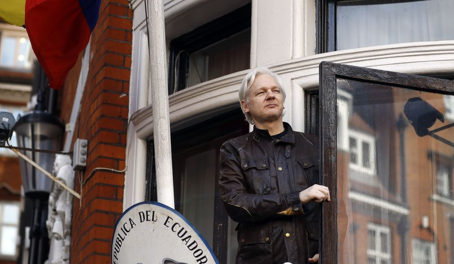 In this Friday May 19, 2017, file photo, WikiLeaks founder Julian Assange greets supporters outside the Ecuadorian embassy in London. Britain's Foreign Office said Thursday, Jan. 11, 2018, it has rejected Ecuador's request to grant diplomatic status to Assange, who has been living in the nation's embassy in London since 2012 to avoid arrest by U.K. authorities. (AP Photo/Frank Augstein, File)