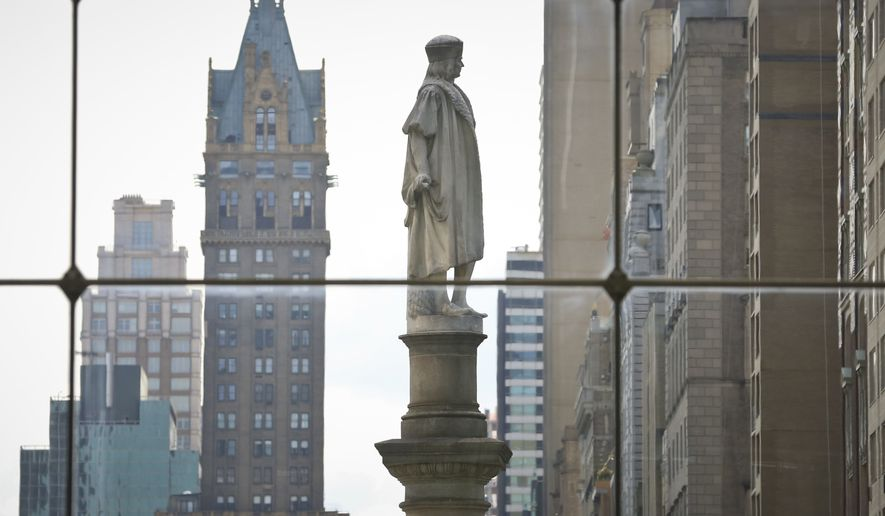 In this Aug. 27, 2017, file photo, the Christopher Columbus statue at Manhattan's Columbus Circle, center, is shown from a view inside the Time Warner Center, in New York. A commission created to figure out what to do with controversial statues and monuments on New York City property has recommended that most be kept where they are with historical markers added to give additional context. The commission was criticized for the idea that statues like those of Christopher Columbus in Columbus Circle could be removed. (AP Photo/Bebeto Matthews, File)