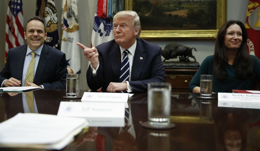 President Donald Trump, joined by Kentucky Governor Matt Bevin, left, and Brooke Rollins, right, President and CEO of the Texas Public Policy Foundation, points to media before speaking during a prison reform roundtable in the Roosevelt Room of the Washington, Thursday, Jan. 11, 2018. (AP Photo/Carolyn Kaster)