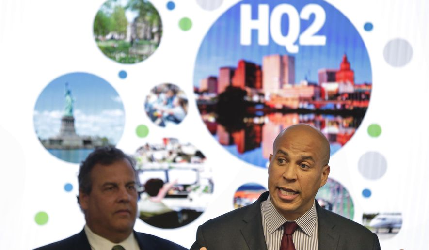 FILE - In this Monday, Oct. 16, 2017, file photo, New Jersey Sen. Cory Booker, right, speaks while New Jersey Gov. Chris Christie stands behind him during an announcement in Newark, N.J. New Jersey lawmakers have signed off on $5 billion in tax breaks to Amazon in an effort to convince the company that Newark would be the best location for the company's planned second headquarters. (AP Photo/Seth Wenig, File)