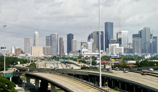FILE - In this May 20, 2010, file photo, cars travel along a highway with the skyline of downtown Houston in the background. Houston is one of the many cities vying to land Amazon's second headquarters. While Texas cities trying to land the new headquarters have been vocal about why they think they should win, they've resisted releasing copies of their proposals. (Michael Paulsen/Houston Chronicle via AP, File)