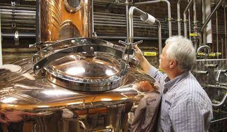 FILE - In this Wednesday Nov. 13, 2013, file photo, Charlie Downs, the artisanal craft distiller at a new Heaven Hill Distilleries tourism attraction in downtown Louisville, Ky., checks gauges on a still that will produce small batches of whiskey. In an effort to woo Amazon's second headquarters to their area, Louisville is playing up its role as the gateway to Kentucky bourbon country. However, the city isn't saying exactly what incentives they are offering to Amazon as enticement to build there. (AP Photo/Bruce Schreiner, File)