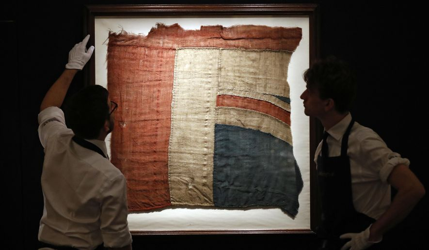 Sotheby's employees look at a frame with a fragment of a Union Jack in London, Thursday, Jan. 11, 2018. An exceptionally large fragment of the Union Flag, which flew from HMS Victory at the Battle of Trafalgar and Love Letters of Britain's Hero, Lord Nelson, to his famous mistress, Lady Hamilton shedding light on the liaison that scandalised 18th-century in England are on auction at Sotheby's. (AP Photo/Frank Augstein)