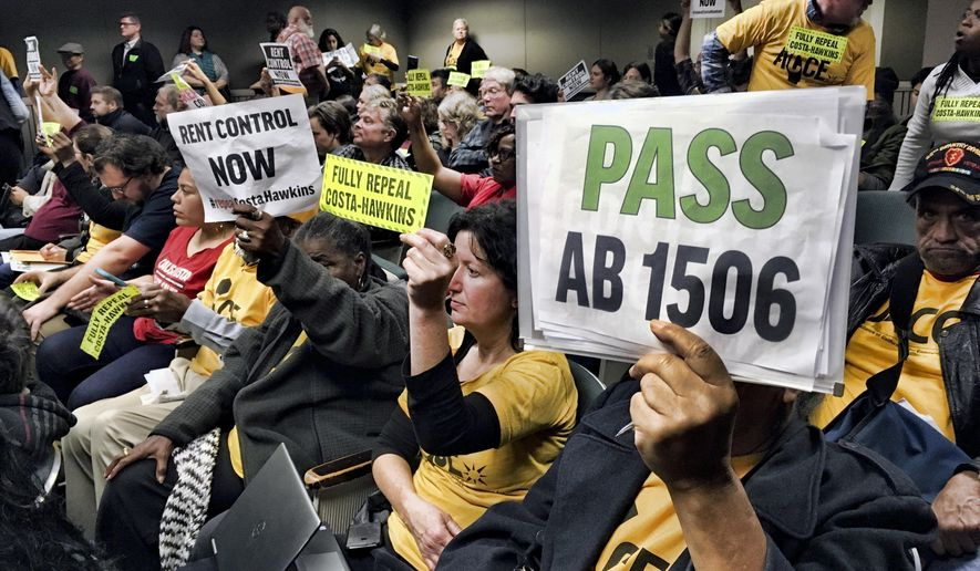 Voters hold signs demonstrating their support for legislation that would allow California communities to expand rent control policies during a legislative hearing in Sacramento, Calif., on Thursday, Jan. 11, 2018. The proposal would repeal a law known as the Costa-Hawkins Act that limits cities' ability to adopt rent control measures on properties built after 1995. (AP Photo/Kathleen Ronayne)