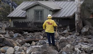 A firefighter walks among the rocks and mud left by a mudslide Wednesday, Jan. 10, 2018, in Montecito, Calif. Anxious family members awaited word on loved ones Wednesday as rescue crews searched grimy debris and ruins for more than a dozen people missing after mudslides in Southern California destroyed houses, swept cars to the beach and left more than a dozen victims dead. (AP Photo/Marcio Jose Sanchez)