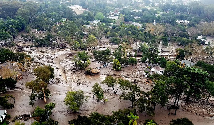 This aerial photo provided by the Santa Barbara County Fire Department shows mudflow and damage to homes in Montecito, Calif., Wednesday, Jan. 10, 2018. Anxious family members awaited word on loved ones Wednesday as rescue crews searched grimy debris and ruins for more than a dozen people missing after mudslides in Southern California on Tuesday destroyed over a 100 houses, swept cars to the beach and left more than a dozen victims dead.  (Matt Udkow/Santa Barbara County Fire Department via AP)