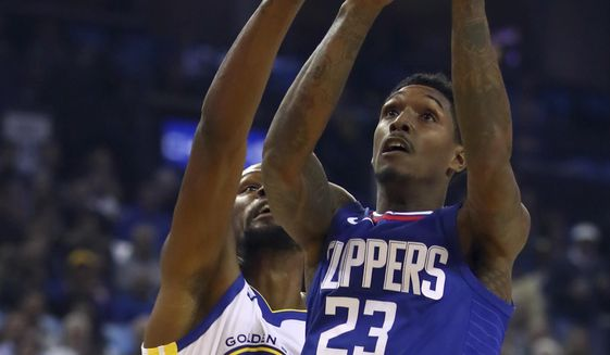 Los Angeles Clippers' Lou Williams (23) shoots past Golden State Warriors' Kevin Durant, left, during the first half of an NBA basketball game Wednesday, Jan. 10, 2018, in Oakland, Calif. (AP Photo/Ben Margot)