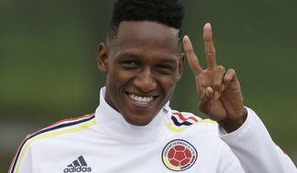 FILE- In this Saturday, March, 25, 2017 file photo, Colombia's Yerry Mina makes a victory signal as he arrives to a training session in Bogota, Colombia. Barcelona said Thursday, Jan. 11, 2018 it has signed Colombia defender Yerry Mina from Brazilian club Palmeiras. (AP Photo/Fernando Vergara, File)
