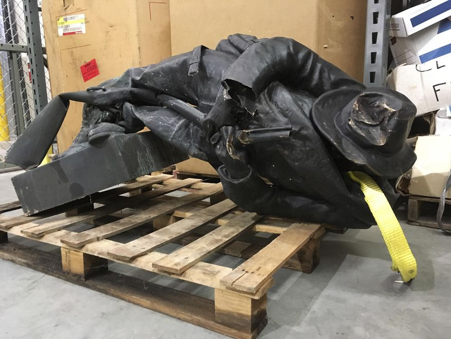 FILE - In this Aug. 15, 2017, file photo, a damaged Confederate statue lies on a pallet in a warehouse in Durham, N.C. The Durham County district attorney said in an email Thursday, Jan. 11, 2018, that he plans to drop felony charges against eight protesters accused of toppling the statue and try them only on misdemeanor charges. (AP Photo/Allen Breed, File)