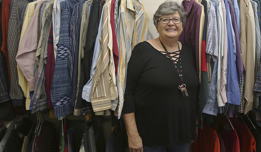 In this Dec. 21, 2017 file photo, Pat Heinecke peers out from a row of clothes for sale at the  Community for Christ Assistance Center in Camp Point, Ill. Heinecke, a former school teacher and principal, is the new director of the center. The center has a thrift store, food pantry and offers emergency rent and utility assistance. Heinecke, a retired school administer, oversees all of it. (Phil Carlson/The Quincy Herald-Whig via AP)