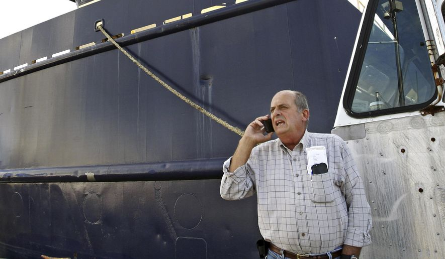 FILE - In this Oct. 14, 2014, file photo, Carlos Rafael talks on the phone at Homer's Wharf near his herring boat F/V Voyager in New Bedford, Mass. The federal government is trying to keep Rafael, known as the Codfather, out of the seafood business.  Rafael was sentenced in 2017 to nearly four years in prison after pleading guilty to evading fishing quotas and smuggling money to Portugal. (John Sladewski/Standard Times via AP, File)