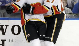 Calgary Flames left wing Micheal Ferland (79) celebrates his goal against the Tampa Bay Lightning with defenseman Dougie Hamilton (27) during the first period of an NHL hockey game Thursday, Jan. 11, 2018, in Tampa, Fla. (AP Photo/Chris O'Meara)