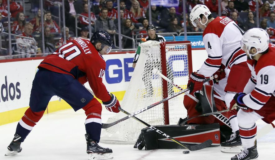 Washington Capitals right wing Brett Connolly (10) tries to shoot as Carolina Hurricanes goalie Scott Darling (33) and defenseman Haydn Fleury (4) defend in the first period of an NHL hockey game, Thursday, Jan. 11, 2018, in Washington. (AP Photo/Alex Brandon)