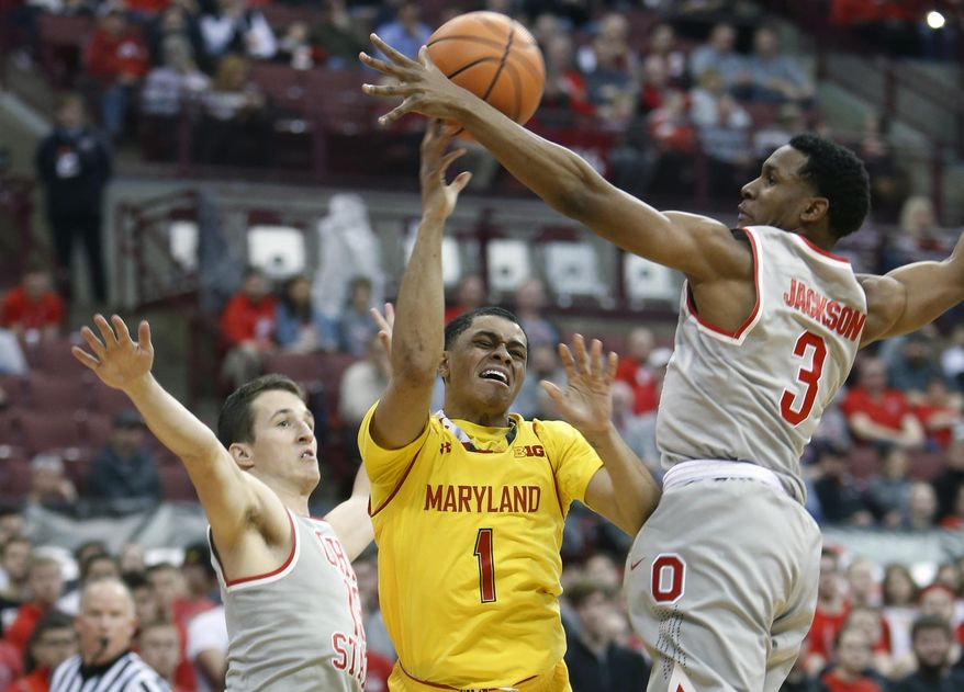 Maryland's Anthony Cowan, center, tries to pass the ball between Ohio State's Andrew Dakich, left, and C.J. Jackson during the first half of an NCAA college basketball game Thursday, Jan. 11, 2018, in Columbus, Ohio. (AP Photo/Jay LaPrete)