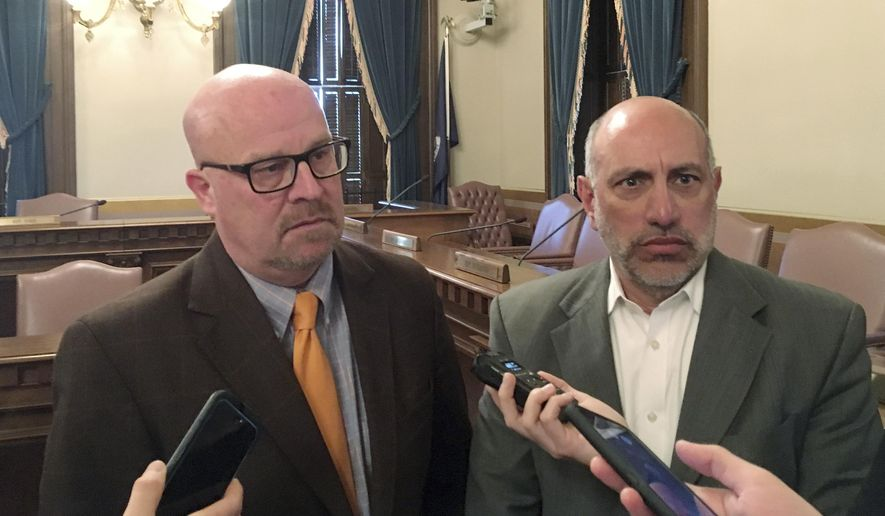 State budget director Al Pscholka, left, and state Treasurer Nick Khouri speak with reporters at the semi-annual revenue-estimating meeting on Thursday, Jan. 11, 2018, at the Capitol building in Lansing, Mich. Gov. Rick Snyder's administration and Republican lawmakers appear to be headed toward a dispute on cutting state taxes by more than what is being proposed to address an unintended consequence of the federal tax overhaul. (AP Photo/David Eggert)