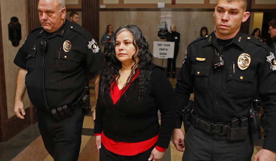 FILE - In this Jan. 9, 2018, file photo, Juanita Gomez is led into Oklahoma County District Court in Oklahoma City. A jury on Thursday, Jan. 11, 2018, convicted Gomez of killing her 33-year-old daughter in 2016 by forcing a crucifix and medallion down her throat because she believed the woman was possessed by the devil. (Steve Sisney/The Oklahoman via AP, File)