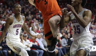 Oregon State forward Tres Tinkle (3) shoots over Arizona guard Allonzo Trier in the first half during an NCAA college basketball game, Thursday, Jan. 11, 2018, in Tucson, Ariz. (AP Photo/Rick Scuteri)