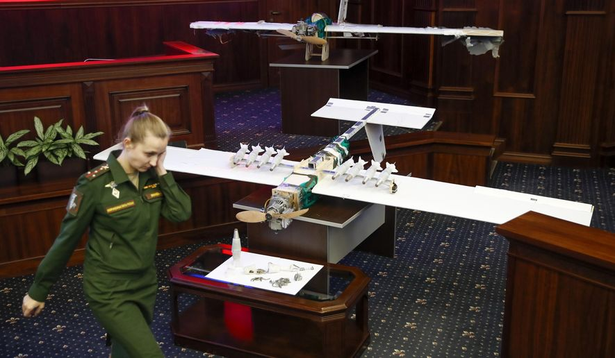 A Russian officer walks next to drones that attacked the Russian air base in Syria and were captured by the Russian military are displayed at a briefing in the Russian Defense Ministry in Moscow, Russia, Thursday, Jan. 11, 2018. Saturday's, Jan.6, 2018 raid against the Hemeimeem air base and a Russian naval facility in Tartus involved 13 drones, seven of the drones were shot down by air defense systems and the remaining six were forced to land, according to the Russian Defense Ministry. (AP Photo/Pavel Golovkin)