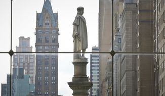 FILE - In this Aug. 27, 2017 file photo, the Christopher Columbus statue at Manhattan's Columbus Circle, center, is shown from a view inside the Time Warner Center, in New York. A commission created to figure out what to do with controversial statues and monuments on New York City property has recommended that most be kept where they are with historical markers added to give additional context. The commission was criticized for the idea that statues like those of Christopher Columbus in Columbus Circle could be removed. (AP Photo/Bebeto Matthews, File)