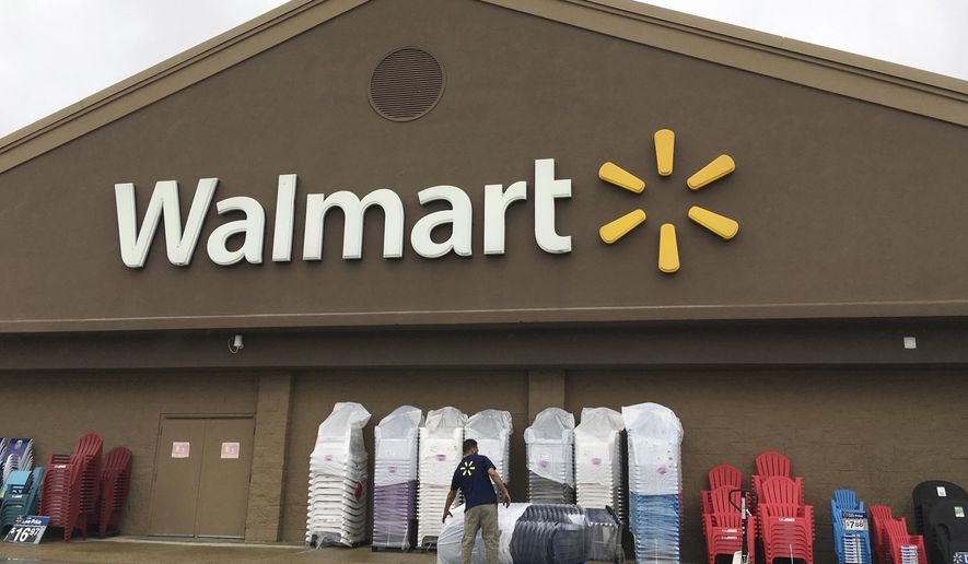 In this June 5, 2017, photo, a worker stacks merchandise outside a Walmart in Salem, N.H. Walmart is boosting its starting salary for U.S. workers to $11 an hour, giving a one-time $1,000 cash bonus to eligible employees and expanding its maternity and parental leave benefits. The retailer said Thursday, Jan. 11, 2018, changes to its compensation and benefits policy will impact more than a million hourly workers in the U.S., with the wage increase effective next month. (AP Photo/Elise Amendola, File)