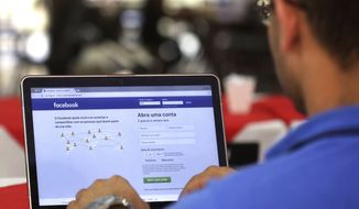 In this Thursday, Jan. 4, 2018, file photo, a man demonstrates how he enters his Facebook page as he works on his computer at a restaurant in Brasilia, Brazil. (AP Photo/Eraldo Peres, File)