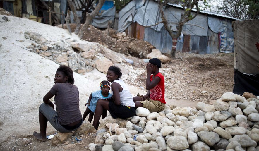 In this Wednesday, Jan. 10, 2018 photo, residents sit at a construction site in the Caradeux refugee camp, set up nearly eight years ago for people displaced by the 2010 earthquake, in Port-au-Prince, Haiti. President Jovenel Moise's government reacted with outrage Friday to reports that President Donald Trump used a vulgar remark to describe the country on the eve of the anniversary of the 2010 earthquake, one of the deadliest disasters in modern history. (AP Photo/Dieu Nalio Chery)