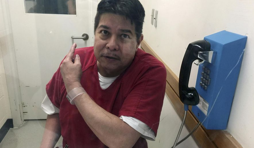 FILE - In this Nov. 17, 2017, file photo, escaped hospital patient Randall Saito points to a guard as he sits in an inmate visitor's booth at San Joaquin County Jail before a scheduled court hearing in French Camp, Calif. Court documents say Saito, who escaped from a Hawaii psychiatric hospital and flew to California, was caught with two high-quality fake IDs, two cellphones and more than $6,000 in cash.  (AP Photo/Terry Chea, File)