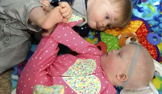 In this December 2017 photo Nicholas and Elizabeth Newby lay on a blanket at their home in High Point, N.C. The pair, who were adopted from Ukraine, both have Down syndrome - a fact that appealed to their adoptive parents, Dwight and Shannon Newby.  (Laura Greene/The High Point Enterprise via AP)