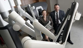 """Surgeons Dr. Mary Dillhoff and Dr. Carl Schmidt with the da Vinci robot at the OSU Wexner Medical Center December 21, 2017. The James Hospital used a new surgical procedure called a Robotic Whipple for the first time last month to remove a pre-cancerous mass on a man from Marion. He is the first patient the James has treated using this """"robotic"""" surgery that is less invasive than traditional surgery, results in less blood loss, smaller incisions with less scarring, and faster recovery time for the patients. (Eric Albrecht/The Columbus Dispatch via AP)"""