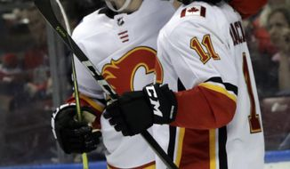 Calgary Flames' Mikael Backlund (11) is hugged by Matthew Tkachuk after scoring an empty-net goal during the third period of an NHL hockey game against the Florida Panthers, Friday, Jan. 12, 2018, in Sunrise, Fla. The Flames won 4-2. (AP Photo/Lynne Sladky)