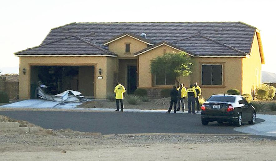 FILE - This Oct. 2, 2017 file photo provided by the Mesquite, Nev., Police Department shows police personnel stand outside the home of Stephen Paddock on Monday, Oct. 2, 2017, in Mesquite. A federal judge is being asked to unseal documents telling what federal agents learned before searching properties belonging to the gunman responsible for the Oct. 1, 2017 massacre on the Las Vegas Strip. Prosecutors aren't opposing a Friday, Jan. 12, 2018 request from media organizations for U.S. District Judge Jennifer Dorsey to release redacted affidavits underlying warrants for locations including Stephen Paddock's home in Mesquite. (Mesquite Police Department via AP, File)