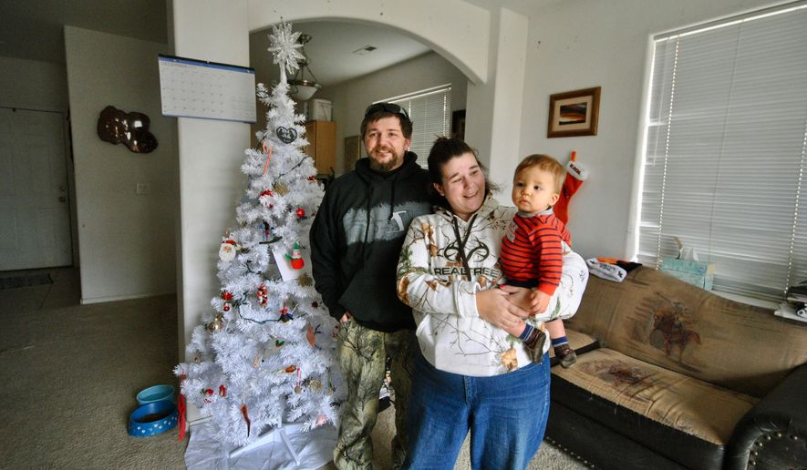 In this December 2017 photo, Eric Ziegler and Amy Fabbrini stand next to their Christmas tree with their son, Hunter at their home in Redmond, Ore. A judge has reunited the Oregon family despite state concerns that the parents are intellectually incapable of caring for their children. (Samantha Swindler/The Oregonian via AP)