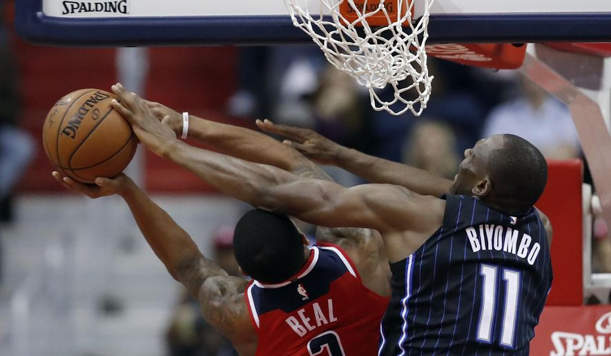 Washington Wizards guard Bradley Beal (3) is fouled by Orlando Magic center Bismack Biyombo (11) during the first half of an NBA basketball game Friday, Jan. 12, 2018, in Washington. (AP Photo/Alex Brandon)