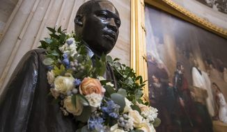 The bust of civil rights activist and leader Martin Luther King Jr. is draped with a wreath of flowers to commemorate his birthday which is observed as a federal holiday next Monday, in the Capitol Rotunda in Washington, Thursday, Jan. 11, 2018. (AP Photo/J. Scott Applewhite)
