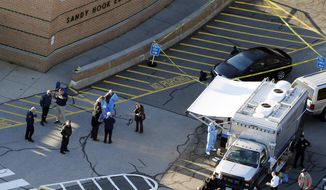 In this Dec. 14, 2012, file photo, officials stand outside of Sandy Hook Elementary School after a shooting in Newtown, Conn. Connecticut State Police are planning to release a report assessing the agency's response to the 2012 massacre at Sandy Hook Elementary School. (AP Photo/Julio Cortez, File) **FILE**