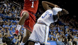 Utah guard Justin Bibbins, left, shoots over UCLA guard Aaron Holiday during the first half of an NCAA college basketball game in Los Angeles, Thursday, Jan. 11, 2018. (AP Photo/Chris Carlson)