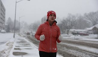 Carlie Glaze runs along Second Street during a snowstorm, Friday, Jan. 12, 2018 in Bloomington, Ind. Glaze said she's walked in the snow earlier and it wasn't too slick so she had the urge to take a run in the snow while she still could do so. (Jeremy Hogan/The Herald-Times via AP)