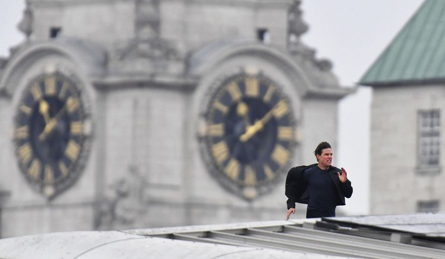 Actor Tom Cruise runs along the rooftop of Blackfriars station, during filming for the new Mission Impossible 6 film, in London, Saturday Jan. 13, 2018. (John Stillwell/PA via AP)