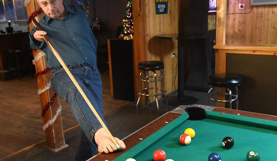 Fifty-five year old Thalidomide baby Paul Pawelko plays pool at the Grand Bar and Restaurant in Roundup, Mont., Dec. 21, 2017. Paul was born with no left arm and only three fingers on a very short right arm. At age 5 he had open heart surgery in an attempt to repair a hole in the upper chamber of his heart. (Larry Mayer/The Gazette via AP)