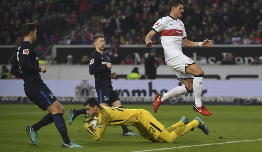 Stuttgart's Mario Gomez, right, challenges with Berlin players, goalie Rune Jarstein, second right, Mitchell Weiser, center, and Niklas Stark during the German Bundesliga soccer match between VfB Stuttgart and Hartha BSC Berlin, in Stuttgart, Germany, Saturday, Jan. 13, 2018. (Marijan Murat/dpa via AP)