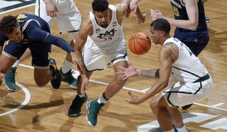 Michigan State's Miles Bridges, front right, and Kenny Goins, center, and Michigan's Isaiah Livers, left, and Jon Teske, right rear, vie for a loose ball during the first half of an NCAA college basketball game, Saturday, Jan. 13, 2018, in East Lansing, Mich. (AP Photo/Al Goldis)