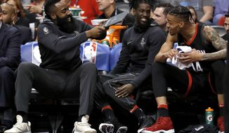 Houston Rockets guard James Harden, left, playfully fans his teammates on the bench during the first half of the team's NBA basketball game against the Phoenix Suns, Friday, Jan. 12, 2018, in Phoenix. (AP Photo/Matt York)