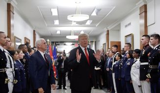 FILE - In this July 20, 2017, file photo, President Donald Trump stops to answer a reporter's question after greeting military personnel during a visit to the Pentagon. Watching is Vice President Mike Pence. With Russia in mind, the Trump administration is aiming to develop new nuclear firepower that it says will make it easier to deter threats to European allies. The plan, not yet approved by President Donald Trump, is intended to make nuclear conflict less likely, but critics argue it would do the opposite. (AP Photo/Pablo Martinez Monsivais)