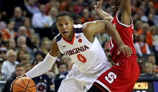 Virginia's Devon Hall drives past North Carolina State's Markell Johnson on Sunday. Hall scored a career-high 25 points in a 68-51 victory. (Associated Press)
