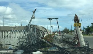 Destroyed power lines, broken utility poles and a demolished building, a result of Hurricane Maria, are seen in the small southern coastal town of Playa Punta Santiago, Puerto Rico on January 1. (Laura Kelly)
