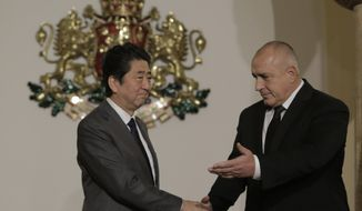 Bulgarian Prime Minister Boiko Borissov welcomes Japanese Prime Minister Shinzo Abe, left, in Sofia, Sunday, Jan. 14, 2018. Abe is visiting Bulgaria as part of his East European tour. (AP Photo/Valentina Petrova)