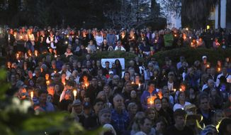 People attend a candlelight vigil in Santa Barbara, Calif., Sunday, Jan. 14, 2018, to pay tribute to the people who were killed when mudslides ravaged a Southern California. (AP Photo/Mike Balsamo)
