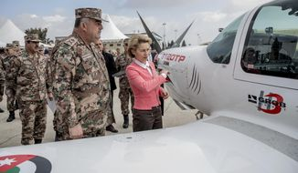 German Defense Minister Ursula von der Leyen, right, and  Jordanian General Mahmoud Freihat  stand next to an exercise plane at Marka airport, Amman, Sunday, Jan. 14, 2018,  prior to a handing over ceremony at. The package handed over included  Mercedes-Benz Zetro off-road trucks, Mercedes Sprinter vans and  GROB G 120TP training aircraft. (Michael Kappeler/Pool Photo via AP)
